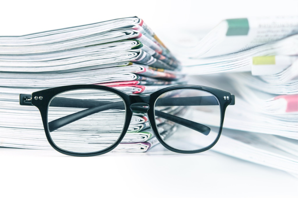 selective-focus-on-reading-eyeglasses-with-stacking-of-newspaper-picture-id609812912